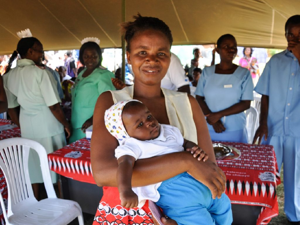 Woman holding an infant at the Launch of Pneumococcal Conjugate Vaccine (PCV).