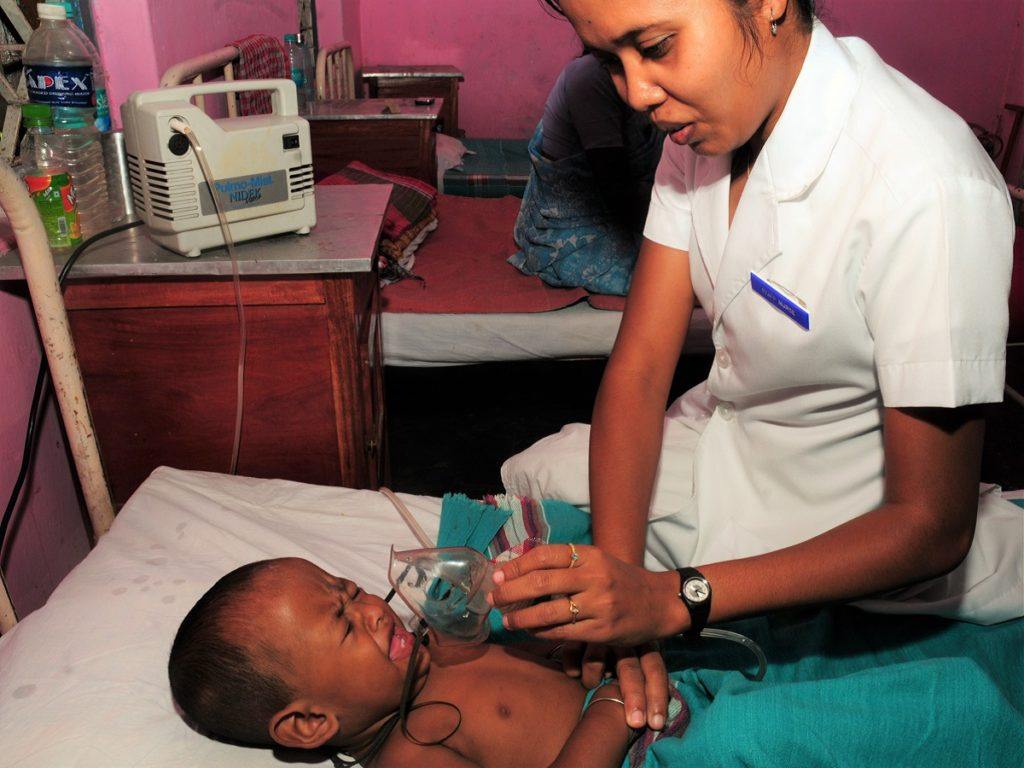 A nursing staff member at a rural health center in the North Andaman Islands of India arranges a nebulizer mask for a child with pneumonia. © 2011 Tushar Sharma, Courtesy of Photoshare